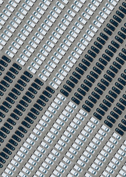 Aerial view of large number of black and white cars arranged in parking lot