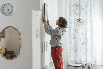 Young woman hanging up picture at home