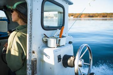 Woman driving shellfishing boat on Narragansett Bay