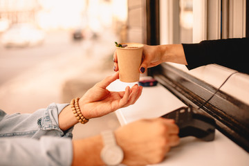 Female barista giving coffee to customer while he making payment