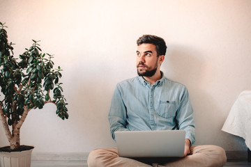 Man using laptop computer while sitting against wall on floor at home