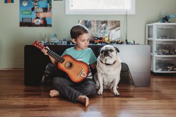 Barefoot boy holding guitar sitting next to pet Pug on hardwood floor
