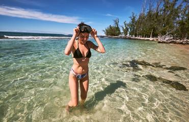 A woman walking in from snorkeling near Makalawena Beach, Hawaii