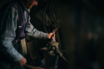 Old man working in the retro blacksmith.