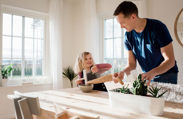 father helping his daughter make her breakfast in the morning at home