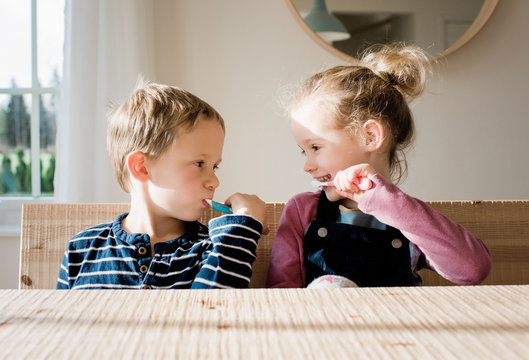 brother and sister brushing their teeth at home before school
