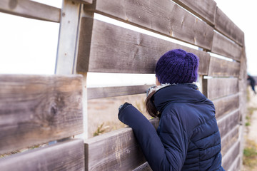 Woman in wool hat leaning, looking to the horizon through wood fence