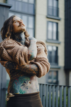 Handsome tattooed sexy man with long hair and mustache outdoors