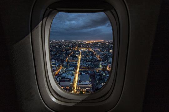 Illuminated Cityscape Seen Through Airplane Window At Night
