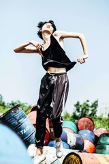 Full length of young woman jumping against oil drums