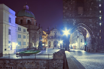 Fotomurales - Night time at Charles Bridge, entrance through Bridge Tower with illumination in Prague, Czech Republic