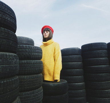 Portrait of woman standing by stacked tires against sky
