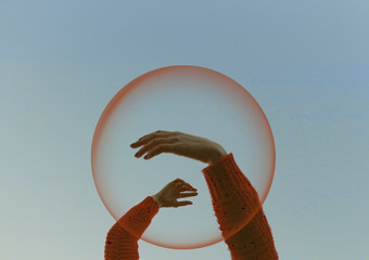 Cropped Hand Amidst Bubble Against Sky
