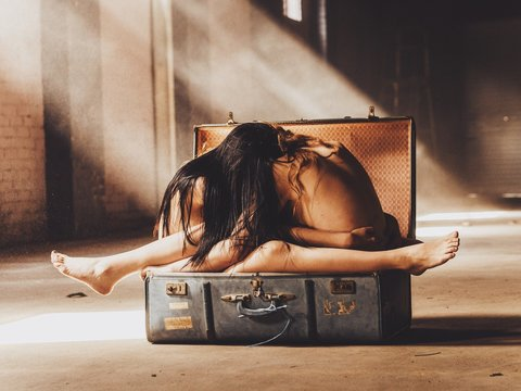 Naked Women Sitting While Embracing In Suitcase