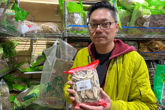 Patrick Siu, manager at Calihouse Nutrition holds a bag of isatis tinctoria root used in traditional Chinese medicine to treat respiratory illness in the Manhattan borough of New York City