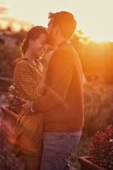 Cheerful couple hugging and kissing at the sunset