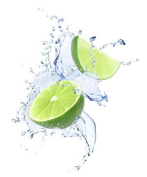 Ripe limes and splashing water on white background