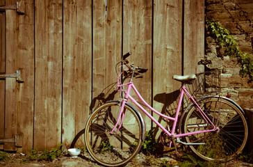 vintage pink bicycle parked against weathered wooden gate background, vintage effect color