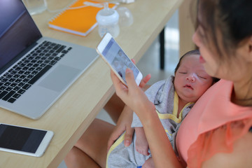 mother playing mobile phone in business home office with cute baby newborn sleeping