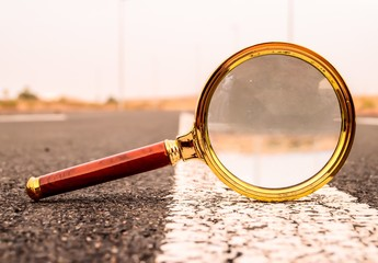 Closeup shot of a magnifying glass on a road street with a blurred background