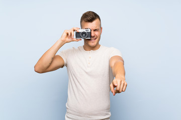 Young handsome blonde man over isolated blue background holding a camera