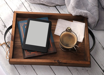 rustic wooden tray with a book, a blank ebook coffee and chocolate on white birch table