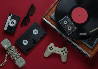 Flat lay retro media and entertainment. Vinyl record player with vinyl record, film camera, video cassette, audio cassette, gamepad, handset on red background. 80s. Top view