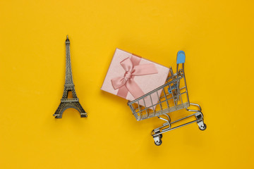 Gift box with bow, statuette of the Eiffel Tower, shopping trolley on yellow background. Shopping in Paris, souvenirs