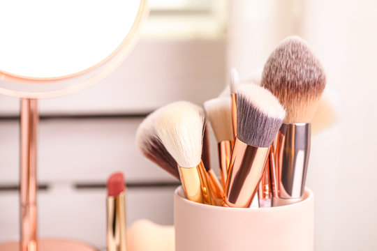 Set of professional makeup brushes in holder, closeup