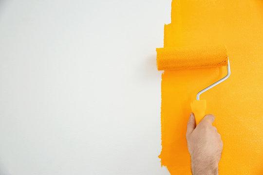 Man painting white wall with yellow dye, closeup. Interior renovation
