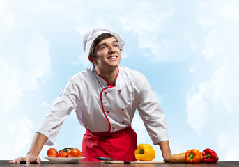Young male chef standing near cooking table