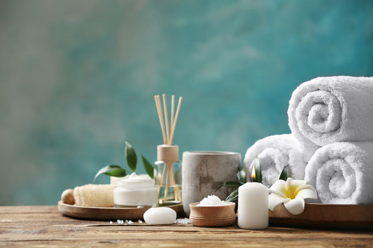 Beautiful spa composition with towels on wooden table against light blue background
