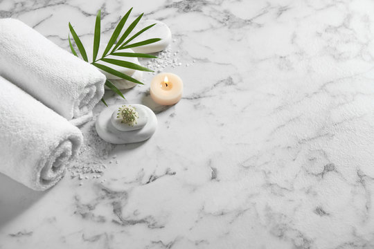 Beautiful composition with spa stones on white marble table, above view