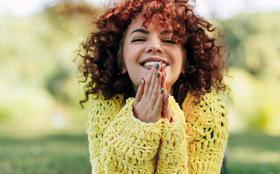 Portrait of cheerful young woman with curly hair smiling broadly with toothy smile. Female has positive expression, wearing yellow sweater and posing against nature background. People, lifestyle