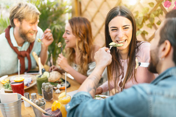 Happy friends lunching with healthy food in bar restaurant - Young people having brunch meal eating and drinking smoothies fresh fruits in vintage bar -  Health trends lifestyle concept
