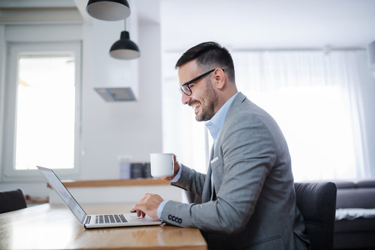 Side view of handsome unshaven caucasian businessman in suit and with eyeglasses sitting at dining table, using laptop and drinking morning coffee. Home interior.