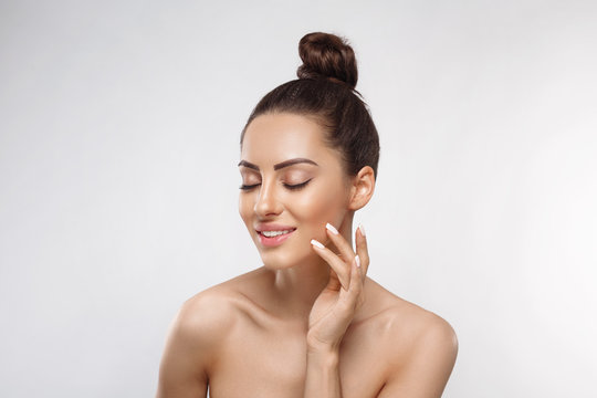 Beauty and Spa Concept. Beautiful Young Woman with Clean Fresh Skin touch face. Facial treatment. Girl Female With Natural Makeup.Cosmetology. Skin Care