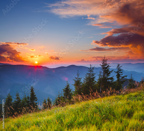 Wall mural Perfect evening landscape in the mountains at sunset. Colorful cloudy sky.