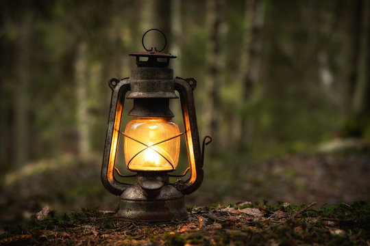 Vintage old lantern lighting in the dark forest. Travel camping concept. Burning lantern on a moss at forest in the night.