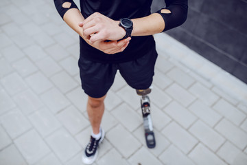 Fotomurales - Cutout picture of caucasian sportsman with artificial leg looking at wristwatch.