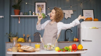 Young Happy Woman Singing And Dancing On Kitchen While Cooking Healthy Food. Fotobehang