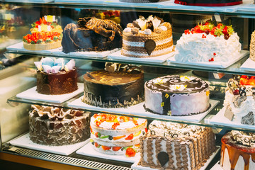 Photo sur Aluminium Boulangerie Various Different Types Of Sweet Cakes In Pastry Shop Glass Display. Good Assortment Of Confectionery