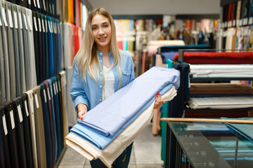 Woman holds fabric in textile store