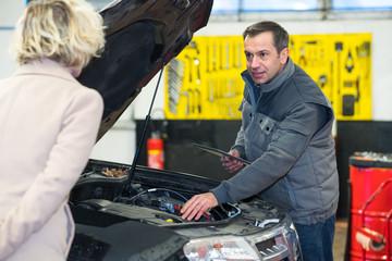 car mechanic with female customer going through maintenance checklist