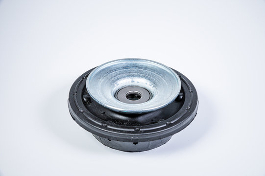 New thrust bearing of front suspension strut of a car on a gray background. The concept of new spare parts and replacement parts in service centers