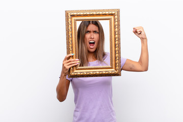young pretty woman feeling happy, excited and surprised, looking to the side with both hands on face with a baroque frame.