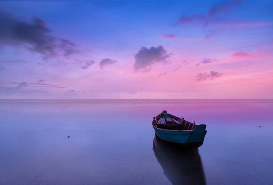 Dramitc sunset with boat on beach