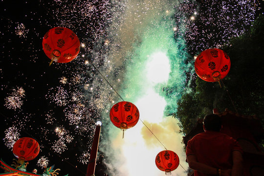 People watch fireworks exploded during Chinese Lunar New Year of the Rat celebrations at a temple in Sidoarjo