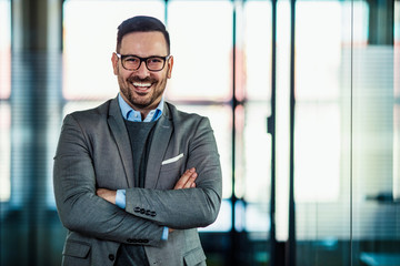 Portrait of a smiling businessman. Portrait of cheerful businessman with arms folded standing in conference room. Happy young business man looking at camera. Portrait of a smiling businessman
