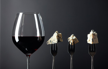 Pieces of blue cheese on a forks and red wine.